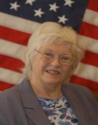photo of Ann Young in front of an American flag
