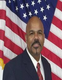 photo of Demetrius Givens in front of an American flag
