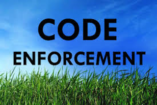 """grass and blue sky with """"code enforcement"""" written in black letters"""